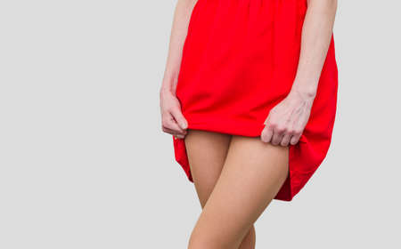 Girl in the red dress lifts the hem, show legs. Women's health, sexuality.