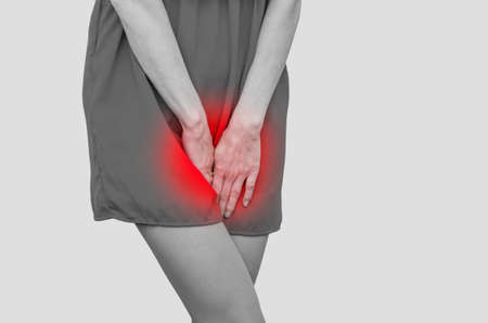 Woman in a red dress holding hands between legs. Experiencing pain, discomfort. Women's health, gynecology.