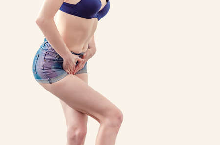Young woman in shorts and a bra is experiencing pain in the uterus, pressed her hands to the lower abdomen. Medical concept. Gynecological problems. Standard-Bild