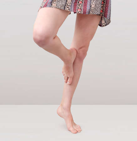 Beautiful female legs on a gray background. One leg is pressed with a foot to the knee, stands on one leg.