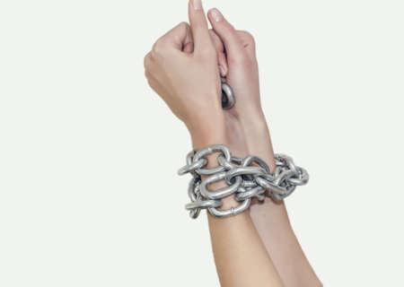 Thin hands woman bound thick shiny metal chain. Slavery, violence, bondage
