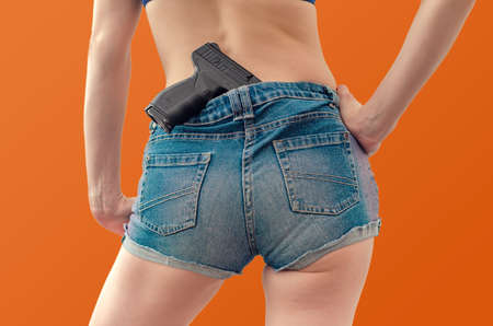 Young girl in denim shorts is holding a black pistol tucked into his belt behind her.