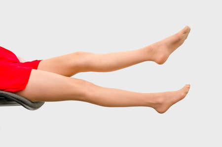 Slender woman legs stretched straight sitting on a chair on a white background. Sexuality, seduction, women's health.