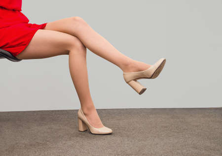 Slender legs of a woman sitting on a chair. Sexuality, seduction, women's health.