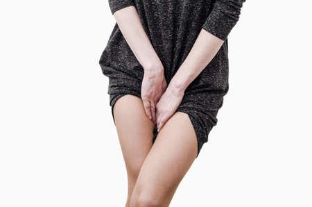 Slim girl in a dark dress shy, hands between legs Zdjęcie Seryjne