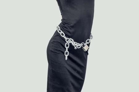 Slim figure girl in black dress. Metal chains on lock around the waist. Slavery, exploitation of people, lack of freedom, violence. Zdjęcie Seryjne