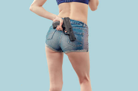young girl in denim shorts is holding a black pistol behind her. Zdjęcie Seryjne