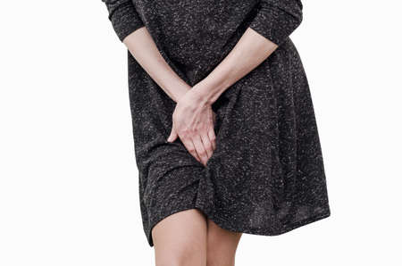 Slender girl in a dark dress experiences discomfort in the uterus, pain, hands between her legs. Incontinence, need to pee in the toilet.