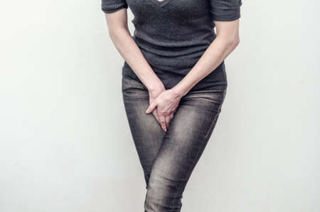 Young slim girl in jeans holds hands pressed between her legs. Women's health, gynecology Zdjęcie Seryjne