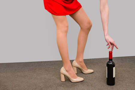 Beautiful legs of a girl in shoes bend down to raise a bottle of wine from the floor.