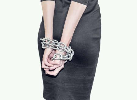 Slim figure girl in black dress. Metallic chains bind hands. Slavery, exploitation of people, lack of freedom, violence.