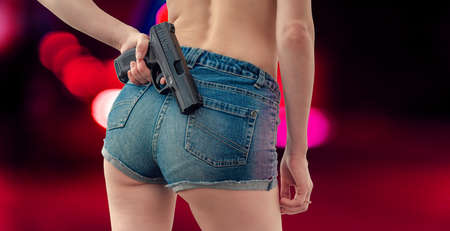 young girl in denim shorts is holding a black pistol behind her. 版權商用圖片
