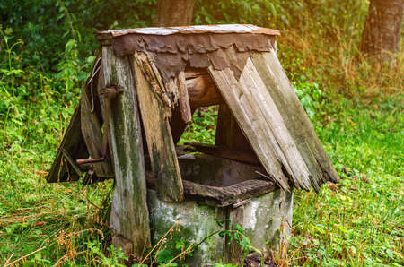 Old abandoned well with a rotten wooden roof in the village.