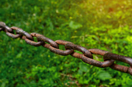 Old rusty chain hanging over green grass background.