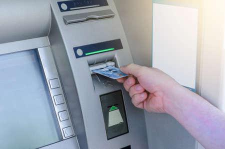 Man hand puts card, press button gray ATM