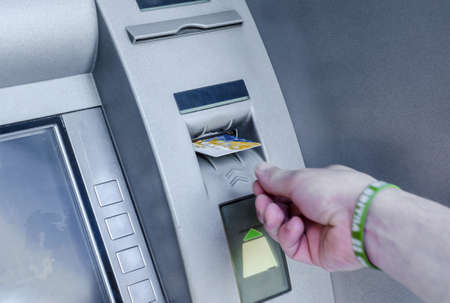 Man hand puts card, press button gray ATM