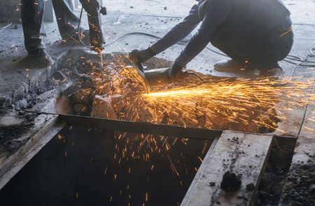 Cutting metal reinforcement in reinforced concrete. Sparks from friction with metal. Disassembly work. Circular electric saw.