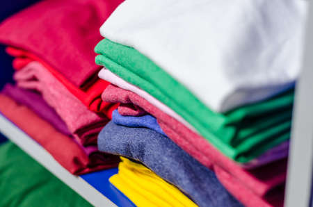 T-shirts made of multicolored fabric stacked in piles 写真素材