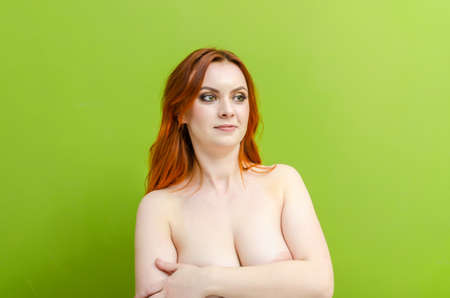 Beautiful naked woman posing on green background. Women's health, cosmetology, body care