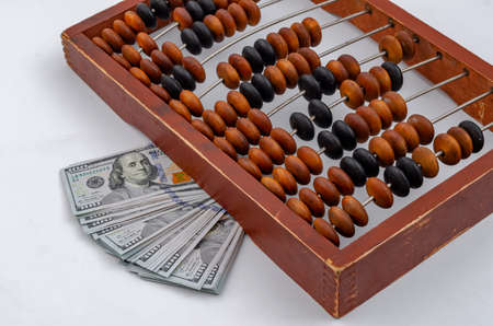 Paper money dollars on vintage wooden abacus background.