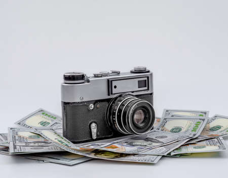 Vintage film camera on scattered American dollars. Concept of earning on photo stocks. Stockfoto