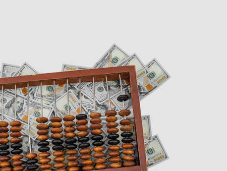 Old wooden abacus on a paper american dollars background. Bookkeeping, profit, business concept