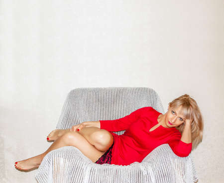 woman in a red short dress with white hair lies on a soft armchair