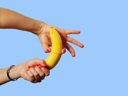 Woman's hands putting on a condom on a yellow banana. Teaching sexual culture, contraceptives, venereal diseases, AIDS