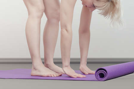 Close up of a woman's arms and legs doing an exercise stretching on a exercise mat and preparing to do yoga. She is training on the rug at home 版權商用圖片