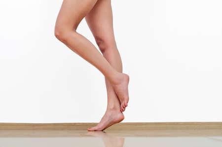 Beautiful woman legs on the floor. Rose on toes. Foto de archivo