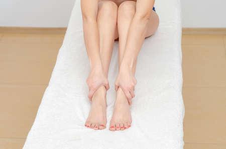 Slender female legs on the floor. One leg raised.