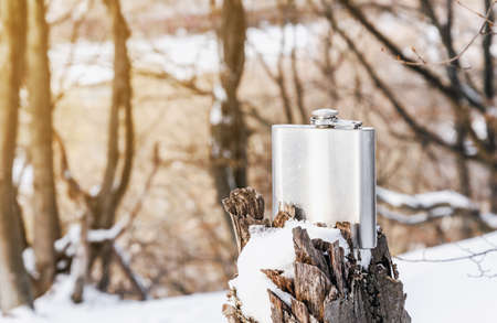 A shiny metal flask for alcohol stands on a tree stump in snow. Nature, winter, rest.