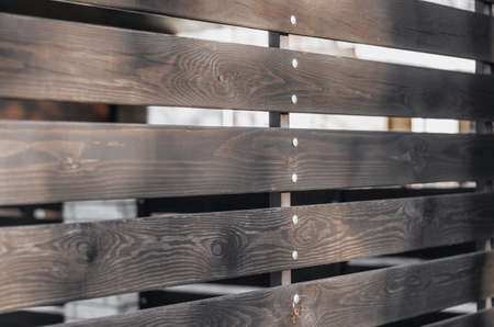 Wooden fence of brown boards with gaps 写真素材