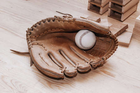 Baseball in glove for playing on wooden background. Handmade, Sports. Game inventory. Manufacture of wood and leather.