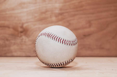 Baseball ball on wooden background. Handmade, Sports. Game inventory. Manufacture of wood and leather.