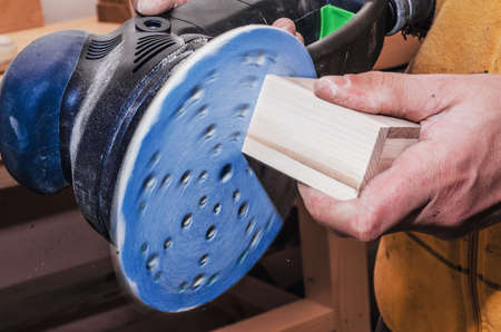 Hands a man polishes a wooden part with a grinding machine. Carpentry production. Working with wood