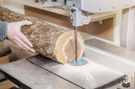 Worker in the carpentry workshop cuts the log into boards using band saw. Joinery. Raw wood Wooden crafts. Work at the factory.