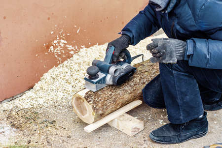 male carpenter grinds a log with hand-held electric planer. Woodwork. Manufacture of wood products. Carpentry workshop