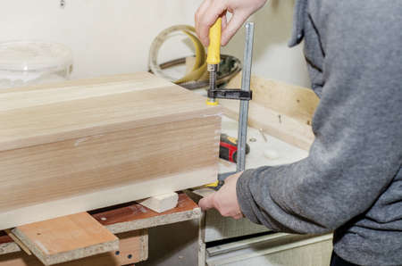 Gluing the wooden box, clamping with clamps. Work in carpentry workshop. Wooden crafts. Fastening parts.
