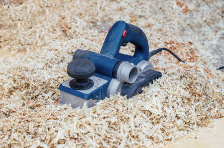 Manual electric planer lies in wood shavings. Woodwork. Manufacture of wood products. Joiner's tool.