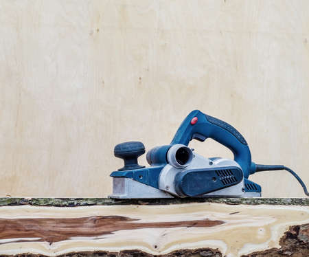 Manual electric plane on raw tree log. Woodwork. Manufacture of wood products. Carpentry workshop