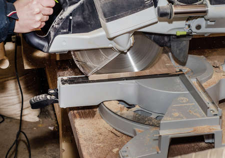 Joiner's machine with circular saw, man cuts the board. Work process, employment, job search, in the enterprise, the manufacture of wooden products