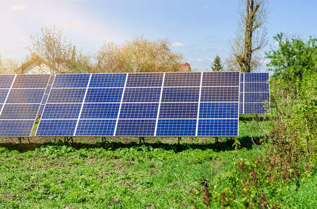 Photovoltaic ecological modules on green grass valley against of sun and cloudy sky.