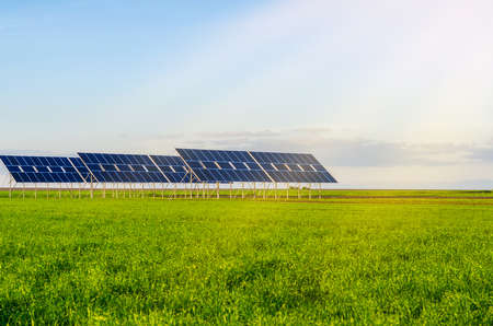 Solar panels in a field on green grass. Environmentally friendly.