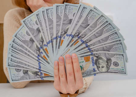 Hand holds american dollars spread out fan.
