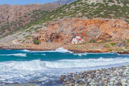 Small Christian church on a rocky shore near the sea.
