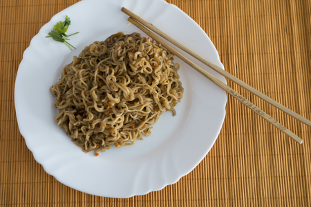 rectangle: Yakisoba  noodles with beef in rectangle plate with bamboo sticks on a table