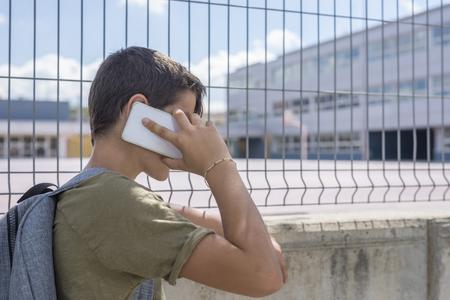 학생이 학교 밖에서 쉬고 휴대 전화로 노는 중