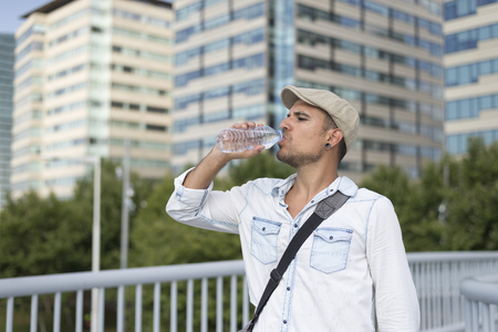 man drinking water: Young and masculine man drinking a water outside