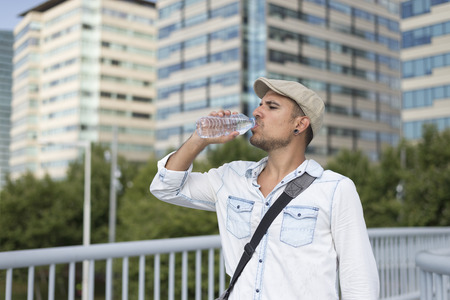 Young and masculine man drinking a water outside